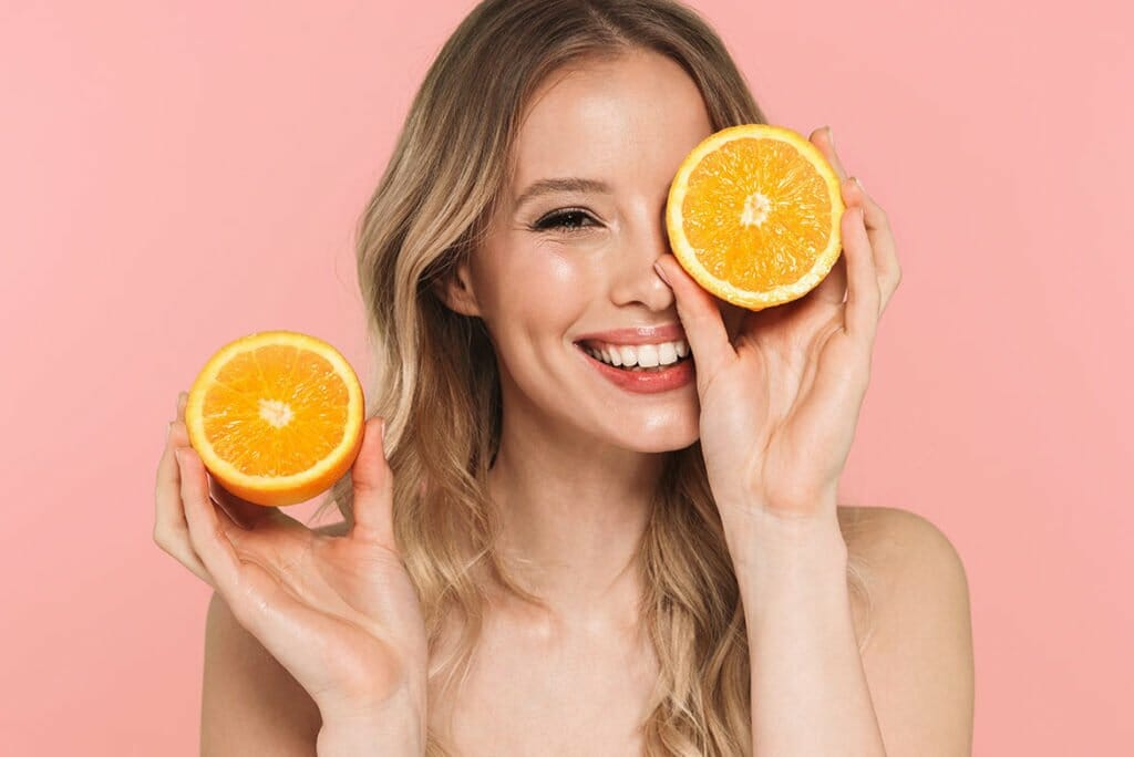 Woman Smiling with Oranges after Get Well IV Vitamin Therapy and Shots Spa Treatment in Lamont, Illinois at Solana Aesthetics and Wellness